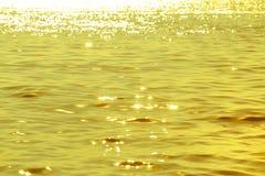 Abstraktes Bild des Oberflächenwassers von Meer oder von Ozean zur Sonnenuntergangzeit mit goldenem Licht Lizenzfreie Stockfotos
