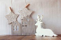 Abstraktes Bild des weißen hölzernen Rens und des Funkelns spielt das Hängen am Seil über Funkelnsilberhintergrund die Hauptrolle Stockbilder