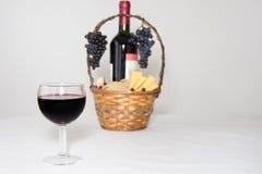 Abstraktes Bild eines Glases Weins Eine Flasche des Rotweins, der Trauben und des Picknickkorbes mit Käsescheiben auf weißem Hint Stockfotografie