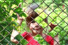 Abstraktes Bild eines kleinen Mädchens hinter Kettengliedzaun foto Stockfotos