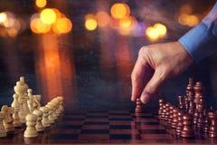 Abstraktes Bild Geschäftsmannhandder beweglichen Schachzahl über Schachbrett Geschäft, Wettbewerb, Strategie, Führung und Erfolg  Stockfotografie