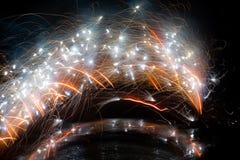 Abstraktes Bild von Funken von einem Feuerwerksbrunnen in einem Bogen über dem Bild mit einer geringfügigen Reflexion unten Lizenzfreies Stockfoto