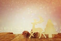 Abstraktes Bild von hölzernen dekorativen Weihnachtsbaum-, Ren- und Kiefernkegeln auf Holztisch und Weihnachtsfeiertag bokeh Lich Stockbilder