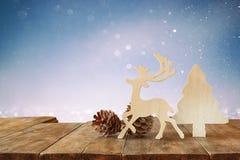 Abstraktes Bild von hölzernen dekorativen Weihnachtsbaum-, Ren- und Kiefernkegeln auf Holztisch und Weihnachtsfeiertag bokeh Lich Lizenzfreies Stockbild