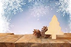 Abstraktes Bild von hölzernen dekorativen Weihnachtsbaum- und Kiefernkegeln auf Holztisch- und Weihnachtsfeiertag bokeh Lichtern  Stockfoto