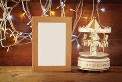 Abstraktes Bild von weißen Karussellpferden der alten Weinlese mit Girlandengoldlichtern und von leerem Rahmen auf Holztisch Retr Stockbilder