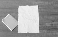 Abstraktes Blatt des einfarbigen, Weißbuches, tapezieren zerknittert auf einem Holz Lizenzfreies Stockbild