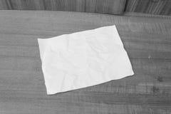 Abstraktes Blatt des einfarbigen, Weißbuches, tapezieren zerknittert auf einem Holz Lizenzfreie Stockfotografie