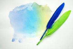 Abstraktes buntes Aquarell auf Weißbuch mit Federn Lizenzfreies Stockbild