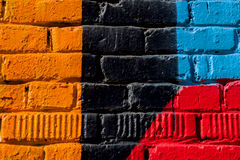 Abstraktes Detail der Backsteinmauer mit Fragment von bunten Graffiti Städtische Kunstnahaufnahme Konzept von modernem ikonenhaft Lizenzfreie Stockbilder