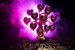 Abstraktes Feld mit Baum und Herzen auf ihm hinter dunklem nebeligem getontem Himmel Liebesbaum von Träumen Valentinsgrußkonzepth Lizenzfreie Stockfotos