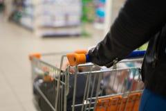 Abstraktes Foto der Frau einen Warenkorb oder eine Laufkatze tragend lizenzfreie stockfotografie