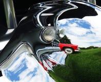 Abstraktes Foto eines roten ` 55 Thunderbird reflektierte sich im Chrom von alten Cadillac Stockfotografie
