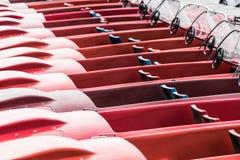 Abstraktes Foto von roten Tretbooten machte an der Anlegestelle auf einem See fest Stockfotos