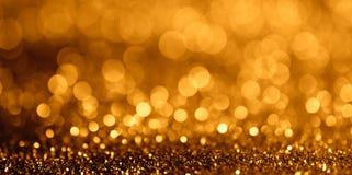 Abstraktes Funkeln bokeh Licht auf breiter Fanseite des goldenen Hintergrundes Lizenzfreie Stockfotos