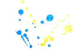 Abstraktes gelbes Spritzen der blauen Tinte Stockfotografie