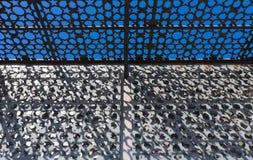 Abstraktes geometrisches Muster des Sonnenscheins durch Metallgitter Lizenzfreie Stockfotografie