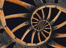 Abstraktes gewundenes hölzernes Lastwagenkanonenrad mit schwarzen Metallklammern, Niete Kanten-Speichenhintergrund des Rades hölz Stockfoto