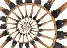 Abstraktes gewundenes hölzernes Lastwagenkanonenradschwarzmetall klammert Niete ein Fractalhintergrund Speichen des Rades hölzern Stockfotos
