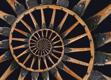 Abstraktes gewundenes hölzernes Lastwagenkanonenradschwarzmetall klammert Niete ein Fractalhintergrund Speichen des Rades hölzern Stockbilder