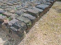 Abstraktes Gitter deckt Felsenmuster und Sandboden mit Ziegeln Stockfotos
