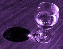 Abstraktes Glas mit Getränk im Veilchen Stockbilder