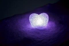 abstraktes Glasherz auf Schnee nachts Karte während eines Valentinstags violettes Herz llight auf schwarzem Hintergrund Stockfoto