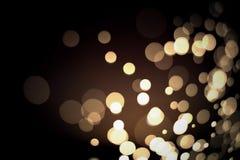 Abstraktes Gold-bokeh mit schwarzem Hintergrund Stockfotografie