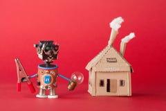 Abstraktes Heimwerkerhauptkonzept Lustige Spielzeugcharakterzangen und Glühlampe in der Hand Plastikbunte Hauptaugen Roboter Stockfotos