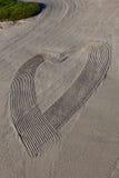 Abstraktes Herz im Sand Stockbilder