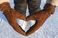 Abstraktes Herz von Handschuhen und von Schlittschuhen im Hintergrund Bokeh Konzept-Liebes-Eislauf Stockbild