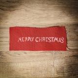 Abstraktes Hintergrundmuster der weißen Sterne auf dunkelroter Auslegung die Aufschrift frohen Weihnachten auf hölzernem Lizenzfreies Stockbild