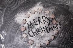 Abstraktes Hintergrundmuster der weißen Sterne auf dunkelroter Auslegung Frohe Weihnachten geschrieben mit Mehl- und Kekssternen Stockfotografie