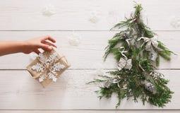 Abstraktes Hintergrundmuster der weißen Sterne auf dunkelroter Auslegung Geschenkboxen auf Tannenbaum am weißen Holz Stockfoto