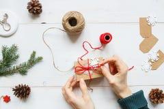 Abstraktes Hintergrundmuster der weißen Sterne auf dunkelroter Auslegung Hände, die Weihnachtsgeschenk auf der hölzernen weißen T Lizenzfreie Stockfotos