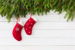 Abstraktes Hintergrundmuster der weißen Sterne auf dunkelroter Auslegung Rote Weihnachtssocken auf weißem hölzernem Hintergrund m Stockbilder