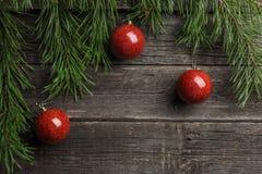 Abstraktes Hintergrundmuster der weißen Sterne auf dunkelroter Auslegung Tannenbaumast rote Weihnachtsballdekorationen am Holztis stockfoto