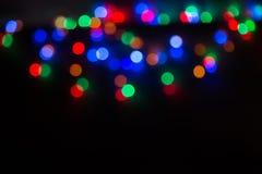 Abstraktes Hintergrundmuster der weißen Sterne auf dunkelroter Auslegung undeutliches rotes Grün und Blaulichter auf einem Schwar Lizenzfreie Stockfotos
