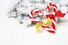 Abstraktes Hintergrundmuster der weißen Sterne auf dunkelroter Auslegung Weihnachtsgrußkarte mit Weihnachtsbaum und Zuckerstange  Stockbild