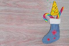 Abstraktes Hintergrundmuster der weißen Sterne auf dunkelroter Auslegung Weihnachtssocke mit Geschenken von Bonbons auf dem Holzt Lizenzfreies Stockbild