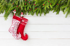 Abstraktes Hintergrundmuster der weißen Sterne auf dunkelroter Auslegung Weihnachtstannenbaum mit Weihnachtssocken auf weißem Hin Lizenzfreies Stockfoto