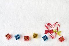 Abstraktes Hintergrundmuster der weißen Sterne auf dunkelroter Auslegung Zuckerstange und kleine Geschenke auf weißem Schneehinte Stockbilder