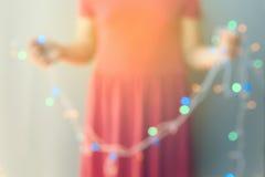 Abstraktes junges Mädchen, das aus Fokus Weihnachtslichtdekorationen heraus hält Unscharfer Hintergrund Stockfotos