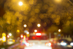 Abstraktes Kreis-bokeh undeutliches gelbes Licht auf der Straße mit weißem Auto der Unschärfe nachts Stockbilder