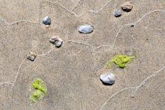 Abstraktes Muster von Wellen auf einem sandigen Strand Stockfoto