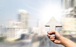 Abstraktes Pfeilzeichen auf der Mannhand, die mit unscharfen Gebäuden b hält Stockfoto