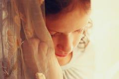 Abstraktes Porträt des durchdachten kleinen Mädchens nahe Fenster Weinlese gefiltertes Bild Stockfotografie