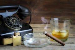 Abstraktes Retro- Stillleben der Zigarre und des Whiskys mit Telefon Lizenzfreie Stockbilder