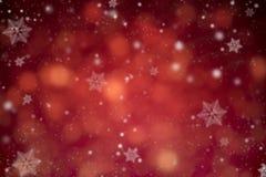 Abstraktes rotes Funkelnbokeh und -schneeflocke Konzeptweihnachten Stockfotografie