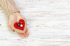 Abstraktes rotes Herz, das in der Hand für Valentinsgruß ` s Tag strickt WeinleseBildträgerfrequenz auf hölzernem bachground Lieb Lizenzfreie Stockfotografie